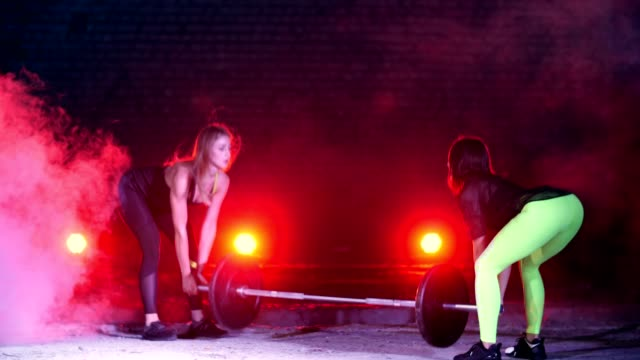 Two athletic girls in pair doing various strength exercises with a barbell, At night, in light of multicolored searchlights, in light smoke, fog, in an old abandoned hangar, video