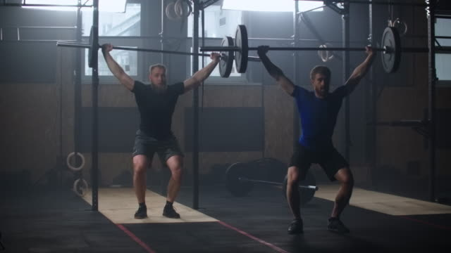 vídeos de stock e filmes b-roll de two athletic male, athletes, doing exercises with the barbell. slow motion. two strong men doing weightlifting with barbell at the gym simultaniously. - agachar se