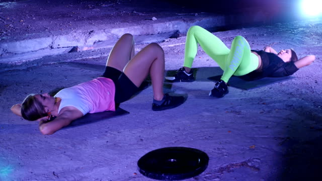 Two athletic, sexy young women, doing fitness exercises in pair, At night, in light smoke, fog, in light of multicolored searchlights, in an old abandoned hangar, building Two athletic, sexy young women, doing fitness exercises in pair, At night, in light smoke, fog, in light of multicolored searchlights, in an old abandoned hangar, building. human back stock videos & royalty-free footage