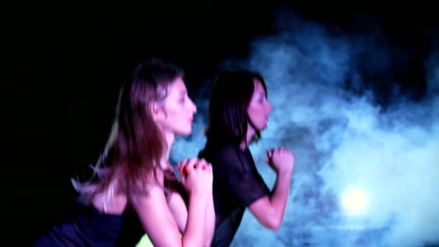Two athletic women, doing fitness exercises . At night, in light smoke, fog, in light of multicolored searchlights, in an old abandoned hangar Two athletic women, doing fitness exercises . At night, in light smoke, fog, in light of multicolored searchlights, in an old abandoned hangar human back stock videos & royalty-free footage