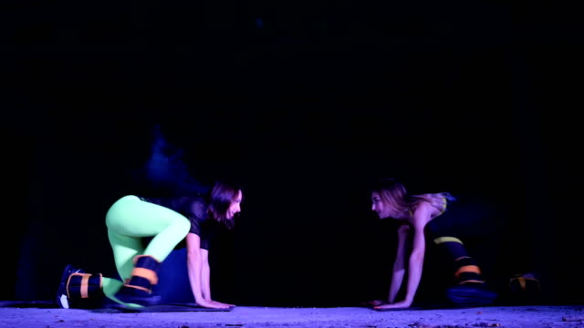 Two athletic women, doing fitness exercises with weighting on their legs, At night, in light smoke, fog, in light of stobascope, in an old abandoned hangar, building Two athletic women, doing fitness exercises with weighting on their legs, At night, in light smoke, fog, in light of stobascope, in an old abandoned hangar, building. human back stock videos & royalty-free footage