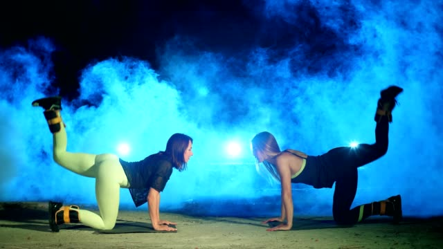 Two athletic women, doing fitness exercises with weighting on their legs, At night, in light smoke, fog, in light of multicolored searchlights, in an old abandoned hangar Two athletic women, doing various fitness exercises with weighting on their legs, At night, in light smoke, fog, in light of multicolored searchlights, in an old abandoned hangar human back stock videos & royalty-free footage