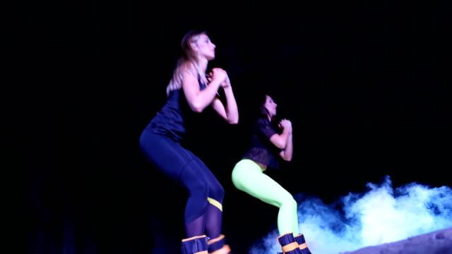 i̇ki atletik kadın, kendi ayakları üzerinde gece, hafif duman, sis, bir eski terk edilmiş hangarda çok renkli projektörler ışığında ağırlık ölçme ile çeşitli fitness egzersizleri yapıyor - i̇nsan sırtı stok videoları ve detay görüntü çekimi