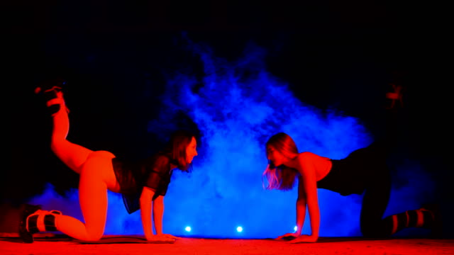 Two athletic women, doing various fitness exercises with weighting on their legs, At night, in light smoke, fog, in light of multicolored searchlights, in an old abandoned hangar Two athletic women, doing various fitness exercises with weighting on their legs, At night, in light smoke, fog, in light of multicolored searchlights, in an old abandoned hangar human back stock videos & royalty-free footage