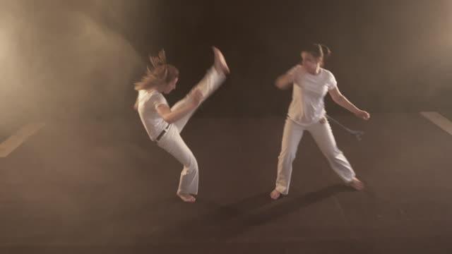 vídeos y material grabado en eventos de stock de dos mujeres atléticas tener una pelea en el entrenamiento deportivo de capoeira. - artes marciales