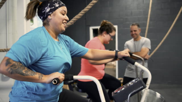 2 つの魅力的な体陽性の女性、ラテン系アメリカ人、白人、コーチ、シニア 55 歳キューバ ヒスパニック男の監督の下でジムでエアロバイクでエクササイズを行う - 肥満点の映像素材/bロール