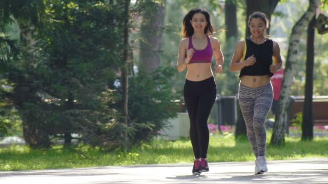i̇ki çekici fitness atletik genç kadın kıvırcık saçlı parkta yaz sabahı, yavaş çalışan spor elbise giymiş - uzun adımlarla yürümek stok videoları ve detay görüntü çekimi