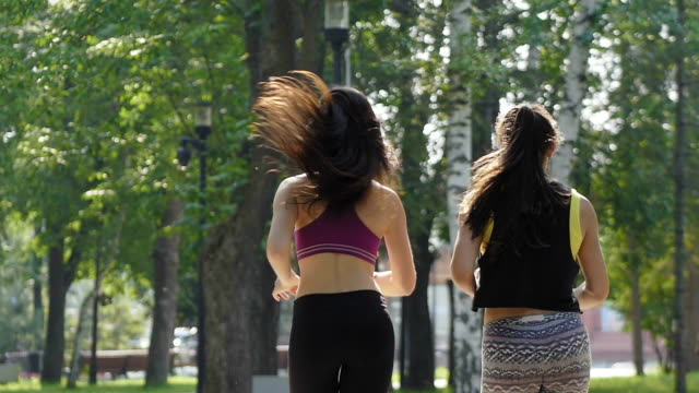i̇ki çekici fitness atletik genç kadın kıvırcık saçlı parkta çalışan yaz sabahı, dikiz, ağır çekim spor elbise giymiş - uzun adımlarla yürümek stok videoları ve detay görüntü çekimi