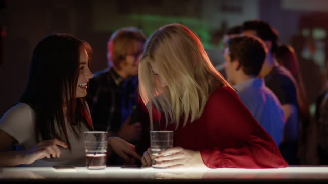 two attractive girls at bar in club talking and laughing video