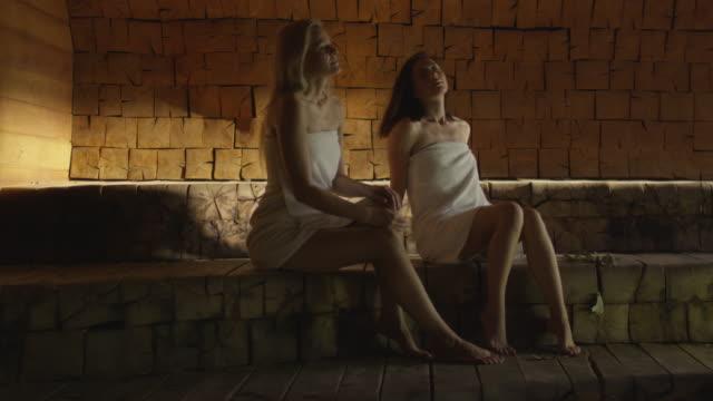 vídeos y material grabado en eventos de stock de dos atractivas chicas en toallas se relaja en un baño de vapor en el spa bienestar centro. - balneario spa