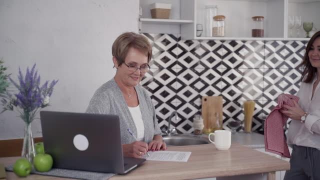 zwei attraktive reife frau sprechen auf küche und mit laptop - vollzeit elternteil stock-videos und b-roll-filmmaterial