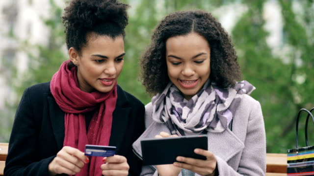 two attractive mixed race women with paper bags sitting on bench and using tablet computer and credit card for online shopping - video di credit card video stock e b–roll