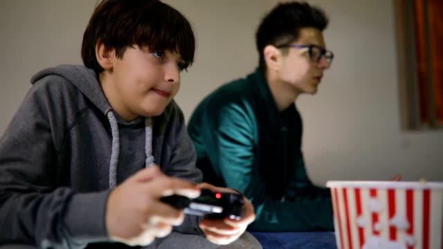 stockvideo's en b-roll-footage met twee aantrekkelijke tienerjongens spelen spelconsole en glimlachend zittend op de bank thuis - sportwedstrijd