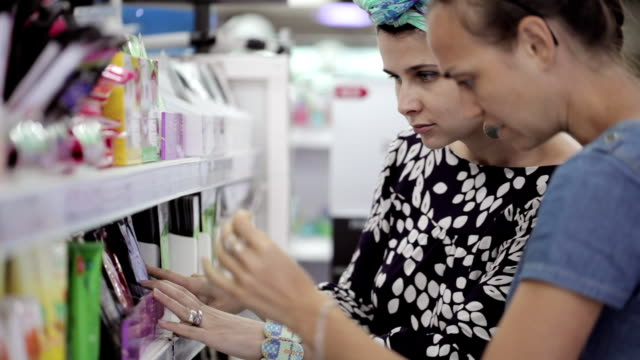 Two attractive women choosing body care products In supermarket. video