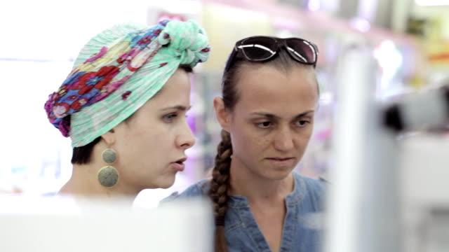 zwei attraktive frauen körper-produkte im supermarkt zu wählen. - kosmetik beratung stock-videos und b-roll-filmmaterial