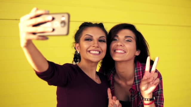 Two attractive women posing while taking selfie and showing peace sign. Beautiful girls taking photos with smart phone standing by the yellow wall. Slowmotion shot video