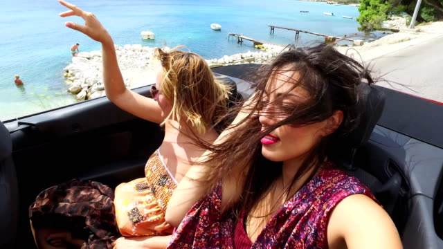 two attractive women riding fast in convertible on seaside highway - lungo video stock e b–roll