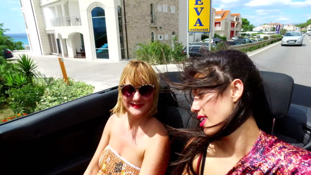 two attractive women riding in the windy back seat of convertible - lungo video stock e b–roll