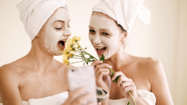 two attractive young women posing while taking selfie on the smartphone sitting inside spa room - facial stock videos & royalty-free footage