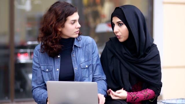 Zwei attraktive junge Frauen draußen zu sitzen und mit Laptop. Interkulturelle Freundschaft. Junge muslimische Frau in schwarzen Hijab ist im Gespräch mit ihrer Freundin kaukasischen. Slowmotion Aufnahme – Video