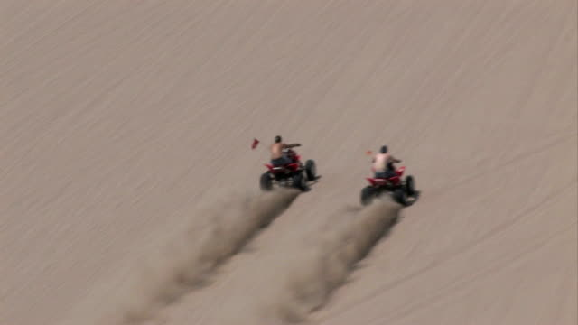 Two ATV race up sand dune