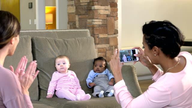 two babies on sofa, mothers photographing - abbigliamento da neonato video stock e b–roll