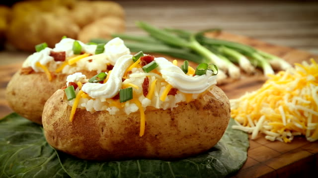 Two baked potatoes fully garnished with fixings. video