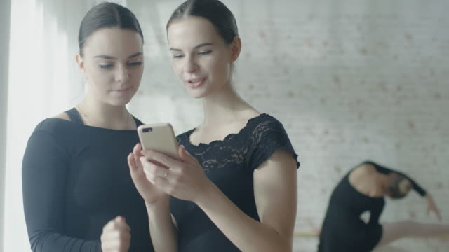 two ballerinas using smartphone computer while third exercises on the barre in the background. shot on a sunny morning in a bright and modern studio. in slow motion. - tutù video stock e b–roll