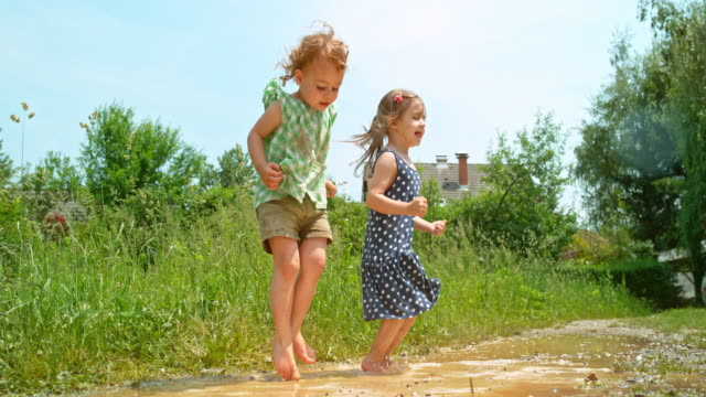 vídeos de stock e filmes b-roll de slo mo two barefoot little girls jumping up and down in a muddy puddle in sunshine - poça