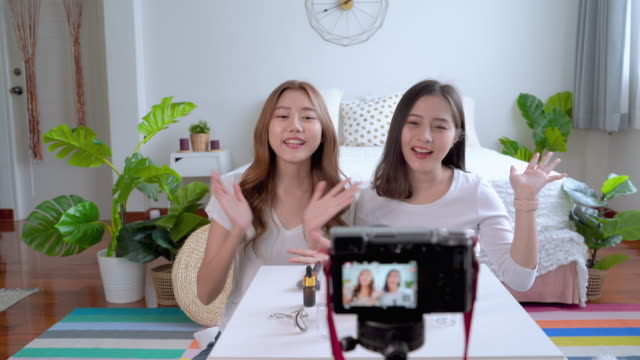 two beautiful asian bloggers are online to review cosmetic products via social media. - tiktok стоковые видео и кадры b-roll
