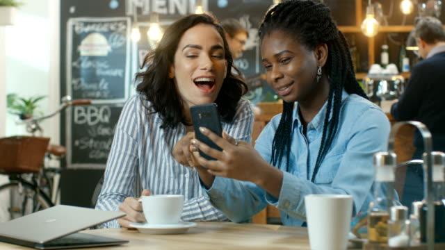 zwei schöne freundinnen sitzen im café und chatten, ein zeigt bilder auf ihrem smartphone, sie beide lachen. in der stilvollen einrichtung hintergrund - klatsch stock-videos und b-roll-filmmaterial