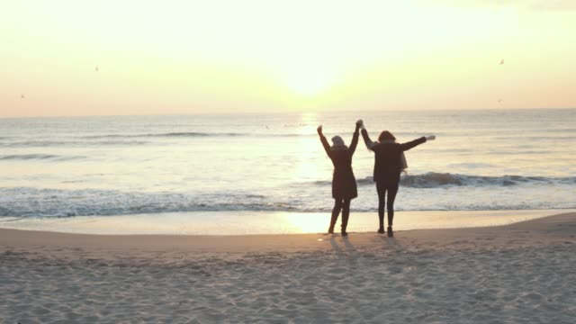 Two beautiful girls have a good time at sea at sunrise or sunset. Girlfriends are walking on the beach.