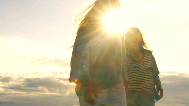 Two Beautiful Girls Holding Hands and Running into the Cloudless Happy Future. Clear Sky in the Background. video
