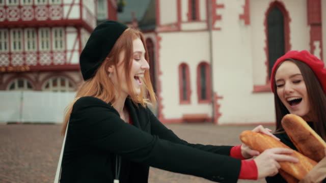 two beautiful girls in black jackets and berets are fighting merrily - francuska kuchnia filmów i materiałów b-roll