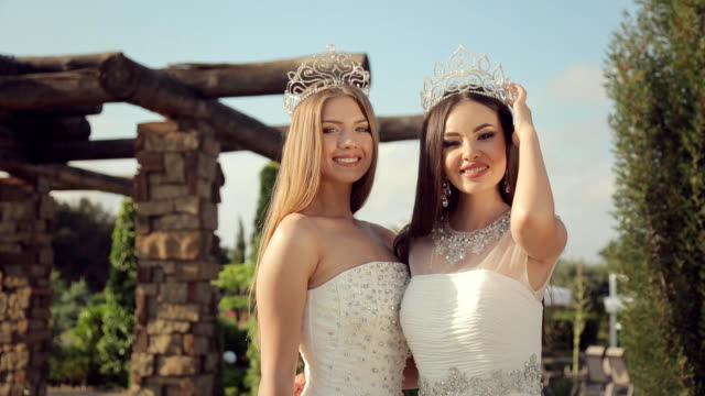 two beautiful girls in elegant white dresses embroidered with stones in the crowns on their head posing in a park on nature - prom fashion stock videos and b-roll footage