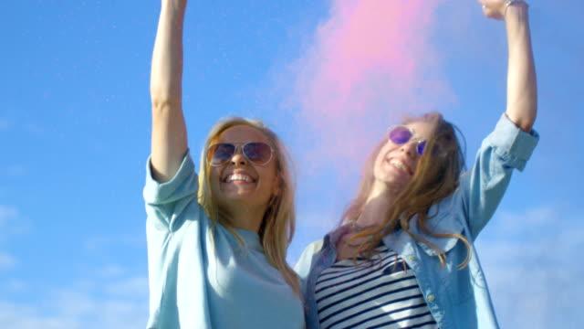 i̇ki güzel sırt kız gülmek ve onlar uçan holi festivali renkli toz kutlamak mutlu. vakit var. clear sky ve blue sea içinde belgili tanımlık geçmiş. - sarı saç stok videoları ve detay görüntü çekimi