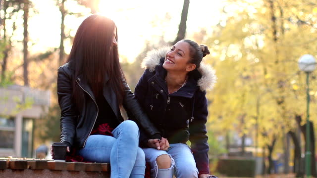 Two Beautiful Lesbian Girls Drinking Coffee Talking And Laughing At Park They Are Sitting On A Bench In The Park And Holding Hands With Autumn Trees On