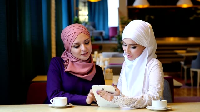 Two Beautiful Muslim Girl Using Tablet In Cafe video