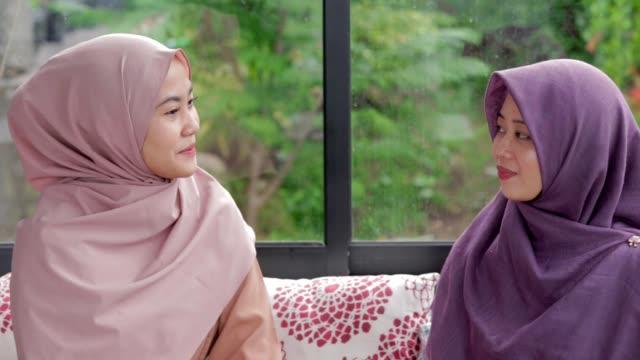 イスラム教徒の 2 つの美しい女性編集のカフェで会合および生 - インドネシア点の映像素材/bロール