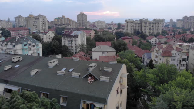 two beautiful people are sitting on the rooftop and playing with drone - serbia video stock e b–roll