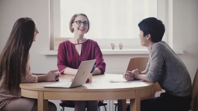Two beautiful positive Caucasian girls talk to Japanese man at a job interview by the table in modern healthy office Two beautiful positive Caucasian girls talk to Japanese man at a job interview by the table in modern healthy office. Young company managers discuss future partnership and consulting at coworking. financial occupation stock videos & royalty-free footage