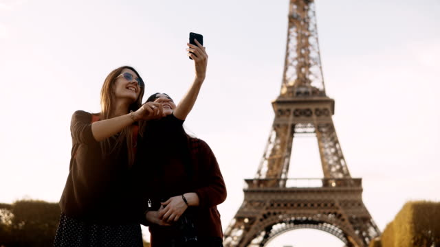 Two beautiful traveling female taking photos on smartphone near the Eiffel tower in Paris, France in sunny day video