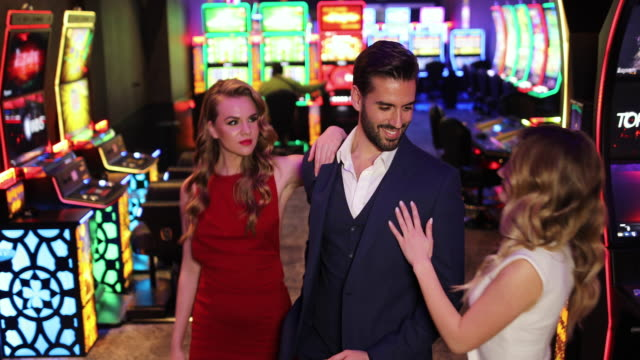 Two beautiful woman and handsome businessman standing at casino and looking at each other video