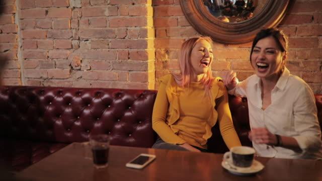 stockvideo's en b-roll-footage met twee mooie vrouw die plezier in een pub - roze haar