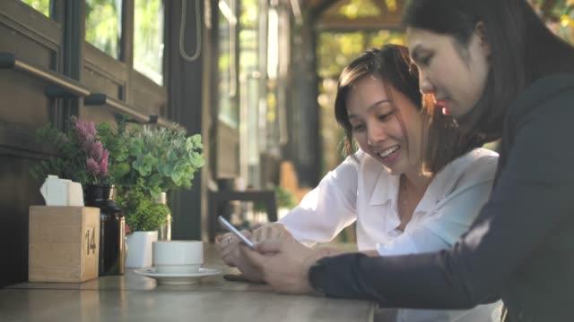 喫茶店に座っておしゃべりする美人女2人 - カフェ文化点の映像素材/bロール