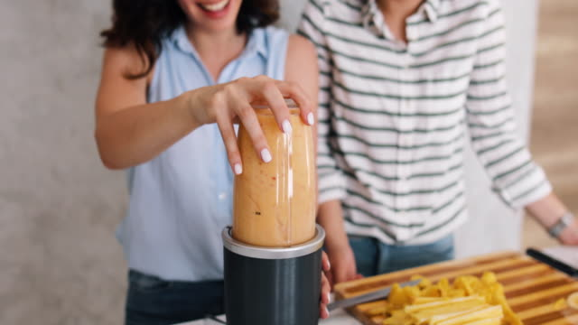 Two beautiful women in their kitchen preparing banana and pineapple smoothies. Young women mix the ingredients, drink smoothies from a glass jar. Healthy way, diet, weight loss concept video