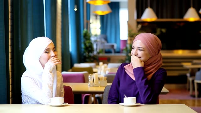 Two beautiful young Muslim women in a cafe communicate and laugh video