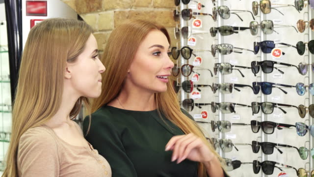 眼鏡店で眼鏡を選択する 2 つの美しい若い女性 ビデオ