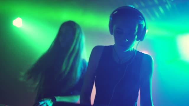 vídeos de stock, filmes e b-roll de duas mulheres bonitas dj tocar a música a mixagem na discoteca - dj