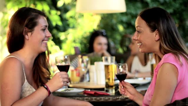 Duas belas mulheres jovens se divertindo bebendo vinho tinto em - vídeo